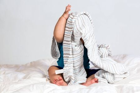 Small Caucasian boy playing under a striped blanket on white duvet bedding