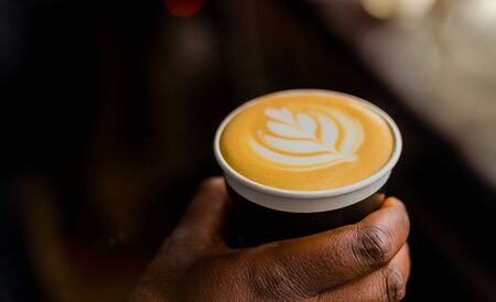 African Coffee Barista holding a take away cup with milk foam in a leaf shape