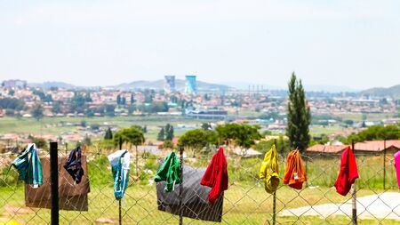 Johannesburg, South Africa - November 16 2012: Clothes and underwear hanging on a fence in suburban Soweto township Stock Photo