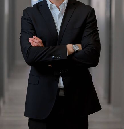 Cropped head Man standing in a smart suit with arms folded