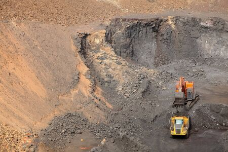 Open pit Manganese Mining - Excavator digging out ore rich rock and loading it onto rock dump trucks for processing