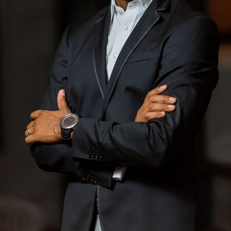 Close-up cropped head of Arab Indian hands and arms of businessman in a suit with folded arms