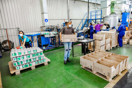 Johannesburg, South Africa - October 19, 2012: Diverse people working on an assembly line in a glue factory Editorial