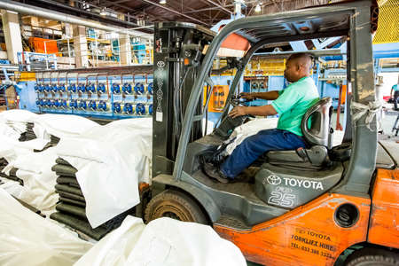 Johannesburg, South Africa - October 19, 2012: African man operating a fork-lift vehicle in a rubber factory Editorial