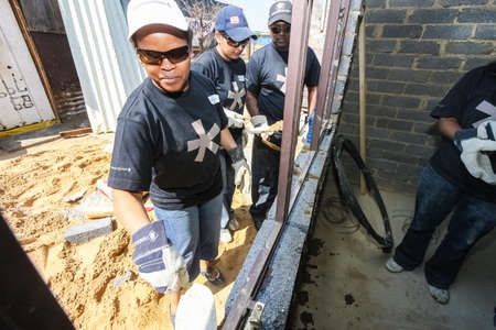 Soweto, South Africa - September 05, 2009: Community Outreach program helping to build a window frame on a small affordable house in local township