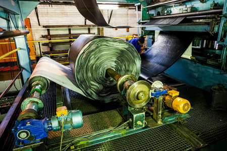 Johannesburg, South Africa - October 16, 2012: African factory worker checking a roll of rubber on a machine in a conveyor belt factory