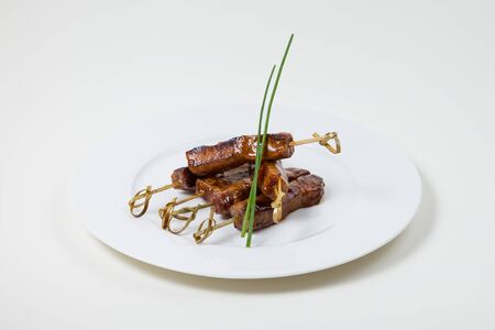 Beef Kebabs on a white plate on a white background isolated