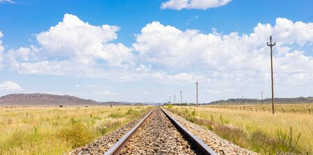 Empty steel railway track in countryside rural farmland area of South Africa