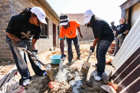Soweto, South Africa - September 05, 2009: Diverse Community Outreach program mixing cement for building a small affordable house