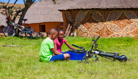 Harrismith, South Africa - October 18 2012: African Children fixing a puncture on a bike