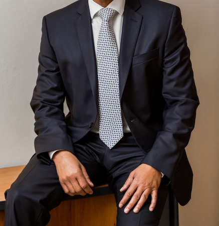 Close-up cropped African Black hands and arms of businessman in a suit sitting down Reklamní fotografie