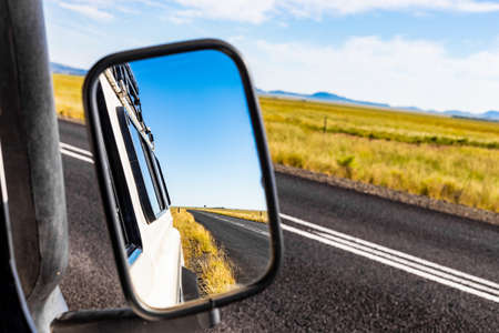 Reflection in a side mirror of a country road behind a 4x4 vehicle