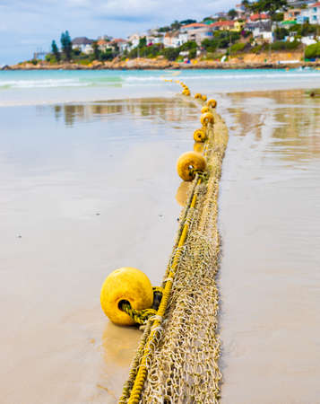 Close-up view of a float of a traditional fishing net on a sandy beach Banque d'images