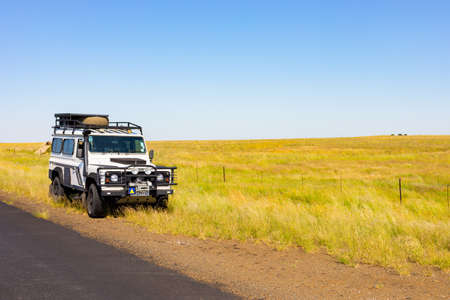 Karoo, South Africa - March 17 2019: Old Land Rover Defender parked beside a national highway in the countryside of South Africa