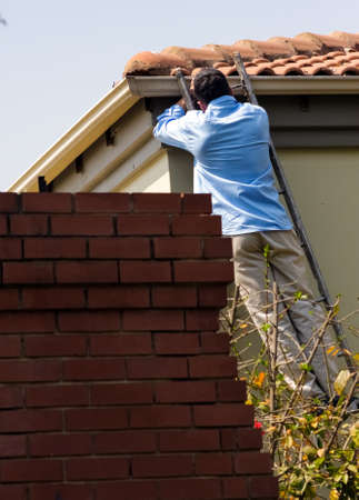 Johannesburg, South Africa - September 10, 2010: White male man working on a ladder on a roof gutter