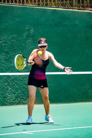 Johannesburg, South Africa - November 10, 2012: Amateur female tennis player practicing on a sunny day