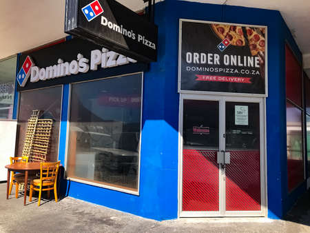 Cape Town, South Africa - December 4, 2020: Closed down Domino's Pizza take away restaurant on high street, due to recession and pandemic related causes