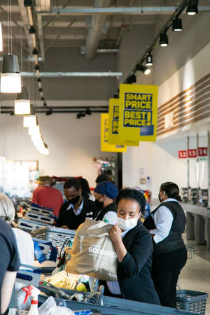Cape Town, South Africa - December 10, 2020: Grocery Store check-out staff and customers wearing face masks during flu pandemic Editorial
