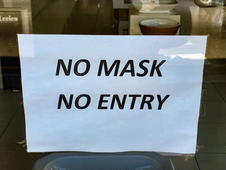 Cape Town, South Africa - December 4, 2020: Information signs on retail shopfront windows, relating to the wearing of masks and other pandemic related regulations Editorial