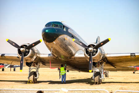 Johannesburg, South Africa - May 22, 2011: Old-school vintage propeller aircraft parked on airport tarmac being checked by mechanic in pre-flight maintenance Editorial