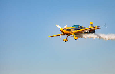 Johannesburg, South Africa - May 22, 2011: Single small propeller airplane performing aerobatics with smoke trails