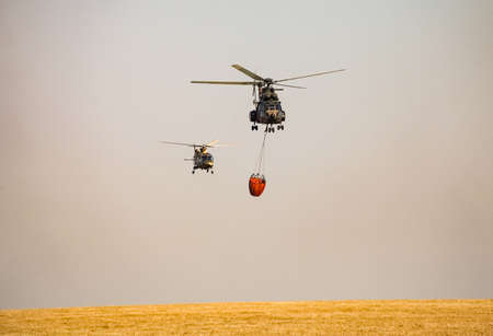 Johannesburg, South Africa - May 22, 2011: Military Air-force fire-fighting helicopter carrying water to extinguish a wild fire