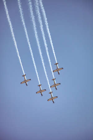Johannesburg, South Africa - May 22, 2011: Small squadron of aerobatics airplanes performing tricks in formation with smoke trails Editorial