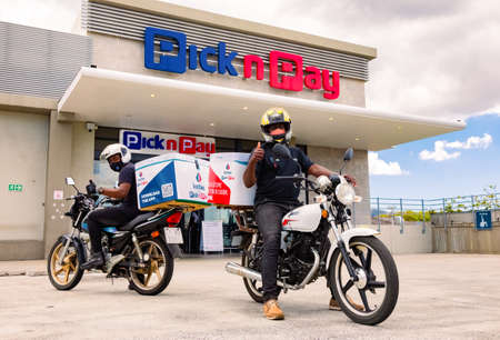 Cape Town, South Africa - December 10, 2020: Express Service home delivery bikes with African riders outside local Pick n Pay grocery store