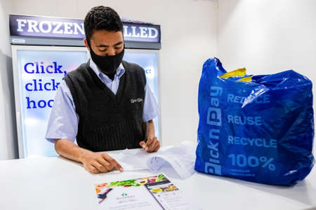 Cape Town, South Africa - December 10, 2020: Staff member checking online grocery order for express home delivery service at local Pick n Pay supermarket