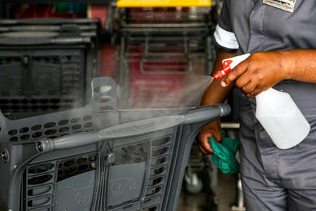 Cape Town, South Africa - December 10, 2020: Staff disinfecting handle of grocery store trolley with alcohol spray sanitizer bottle to protect against spread of virus