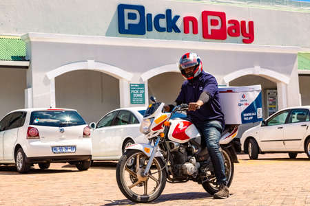 Cape Town, South Africa - December 10, 2020: Express Service home delivery man with bike outside local Pick n Pay grocery store