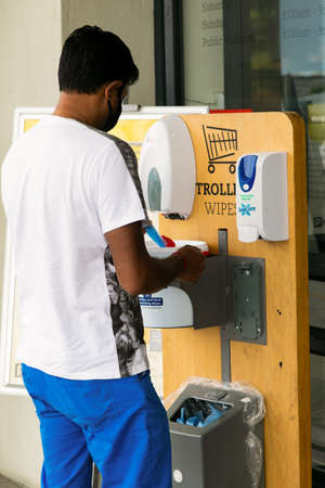 Cape Town, South Africa - December 10, 2020: Man using Hand Sanitizer and trolley wipes outside Pick n Pay grocery store for the prevention of the spread of virus