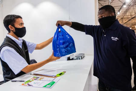 Cape Town, South Africa - December 10, 2020: Express Service home delivery man collecting order from staff at counter inside local Pick n Pay grocery store