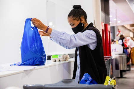 Cape Town, South Africa - December 10, 2020: taff member checking online grocery order for express home delivery service at local Pick n Pay supermarket