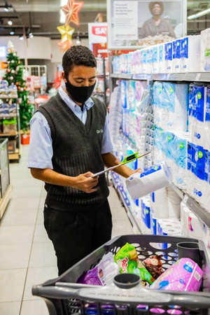 Cape Town, South Africa - December 10, 2020: Staff member picking grocery products from shelf for express home delivery service at local Pick n Pay supermarket Editorial