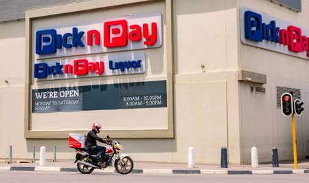Cape Town, South Africa - December 10, 2020: Express Service home delivery bike with African rider on the road outside local Pick n Pay grocery store