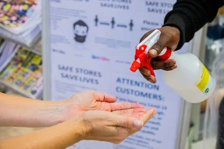 Cape Town, South Africa - December 10, 2020: Staff disinfecting hands of customer at store entrance with alcohol spray sanitizer bottle to protect against spread of virus