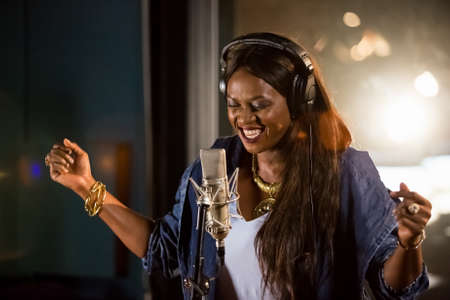 Johannesburg, South Africa - April 29, 2015: Waje Nigerian singer recording vocal part on Afro-pop song in studio