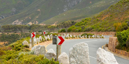 Chevron warning road sign for sharp hairpin bend on mountain pass in Cape Town, South Africa