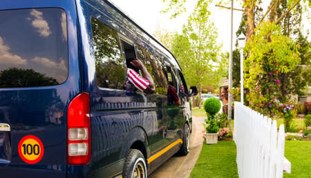 Minibus taxi van parked outside a house in a wealthy neighbourhood with an arm hanging out Banco de Imagens