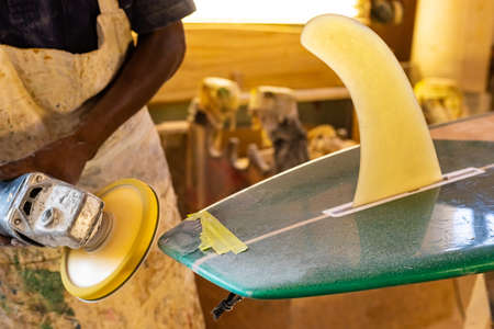 Close up of a African Craftsman surfboard Shaper working in a repair workshop