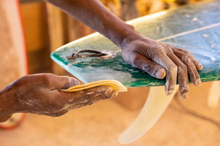 An African Craftsman surfboard Shaper working in a repair workshop with Sandpaper