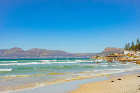 Cape Town, South Africa - March 23, 2021: Surfers and swimmers at Muizenberg beach