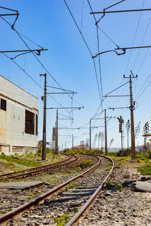 Cape Town, South Africa - March 23, 2021: Electric Railway line on the shoreline of coastal town of Muizenberg