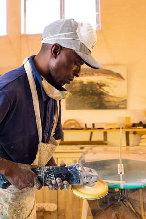 Cape Town, South Africa - March 23, 2021: An African Craftsman surfboard Shaper working in a repair workshop