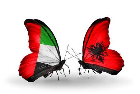arabe: Dos mariposas con banderas en las alas como símbolo de las relaciones de Emiratos Árabes Unidos y Albania