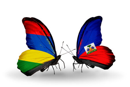 Two butterflies with flags on wings as symbol of relations Mauritius and Haiti photo