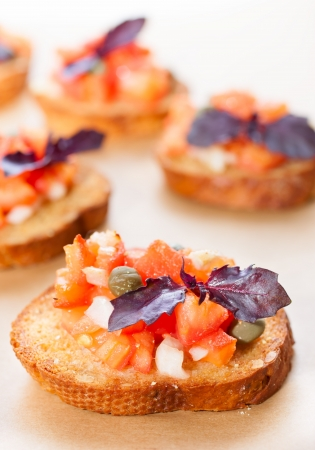 Italian bruscetta with tomatoes and onions, decorated with basil photo