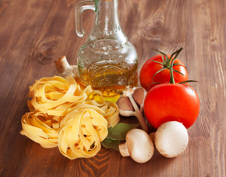 Italian Pasta with tomatoes, olive oil, mushrooms and spices on a wooden background photo