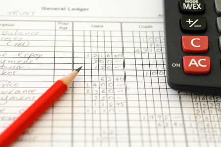 Handwritten Accounting ledger showing bookkeeping using pencil and calculator.